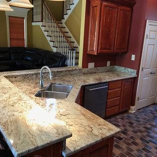 Inredning av ett klassiskt avskilt kök, med en nedsänkt diskho, luckor med upphöjd panel, bruna skåp, granitbänkskiva, rostfria vitvaror, tegelgolv och en halv köksö