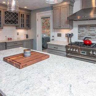 ボストンの大きいトランジショナルスタイルのおしゃれなキッチン (エプロンフロントシンク、レイズドパネル扉のキャビネット、グレーのキャビネット、クオーツストーンカウンター、白いキッチンパネル、セラミックタイルのキッチンパネル、シルバーの調理設備の、クッションフロア、マルチカラーの床、マルチカラーのキッチンカウンター) の写真