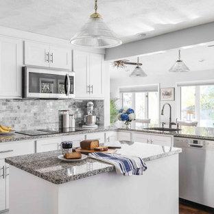 Geräumige Moderne Küche in U-Form mit Waschbecken, Schrankfronten mit vertiefter Füllung, weißen Schränken, Granit-Arbeitsplatte, Küchenrückwand in Grau, Rückwand aus Marmor, Küchengeräten aus Edelstahl, braunem Holzboden, Kücheninsel, braunem Boden und grauer Arbeitsplatte in Providence