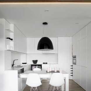 Example of a trendy u-shaped eat-in kitchen design in Barcelona with flat-panel cabinets, white cabinets and white backsplash