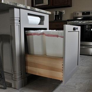 Cette image montre une cuisine américaine craftsman en L de taille moyenne avec un évier 1 bac, un placard à porte shaker, un plan de travail en granite, un électroménager en acier inoxydable, un sol en carrelage de porcelaine, un îlot central et des portes de placard en bois brun.
