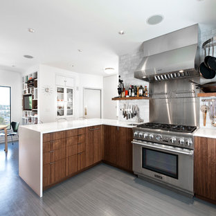 Eat-in kitchen - contemporary eat-in kitchen idea in Seattle with flat-panel cabinets, dark wood cabinets, white backsplash, stone tile backsplash and stainless steel appliances