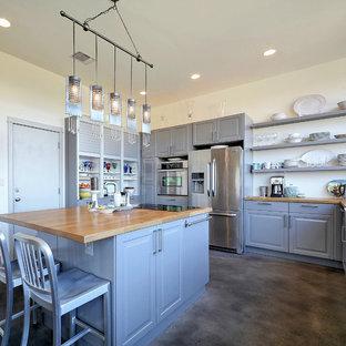 オースティンのトラディショナルスタイルのおしゃれなキッチン (レイズドパネル扉のキャビネット、青いキャビネット、木材カウンター、シルバーの調理設備の、コンクリートの床、グレーの床、ベージュのキッチンカウンター) の写真