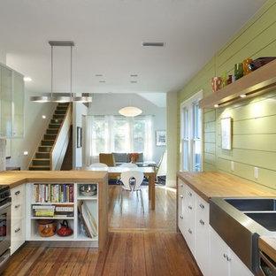 Modelo de cocina rural con fregadero de doble seno, encimera de madera, armarios con paneles lisos, puertas de armario blancas y electrodomésticos de acero inoxidable
