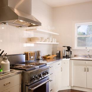 Exempel på ett klassiskt l-kök, med rostfria vitvaror, bänkskiva i rostfritt stål, en nedsänkt diskho, släta luckor, vita skåp och vitt stänkskydd