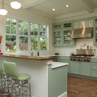 Diseño de cocina en U, tradicional, con armarios tipo vitrina, puertas de armario verdes, salpicadero blanco, electrodomésticos de acero inoxidable y salpicadero de azulejos tipo metro
