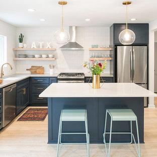 オースティンの中くらいのミッドセンチュリースタイルのおしゃれなキッチン (アンダーカウンターシンク、シェーカースタイル扉のキャビネット、青いキャビネット、白いキッチンパネル、サブウェイタイルのキッチンパネル、シルバーの調理設備、淡色無垢フローリング、ベージュの床、白いキッチンカウンター、人工大理石カウンター) の写真