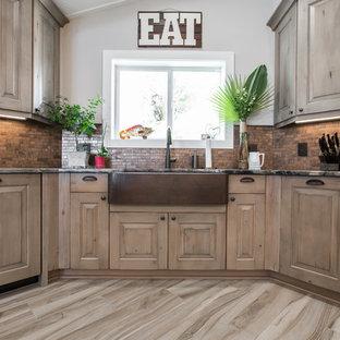Diseño de cocina comedor tradicional, grande, con armarios con paneles con relieve, puertas de armario con efecto envejecido, encimera de cobre, electrodomésticos de acero inoxidable, suelo de baldosas de porcelana y una isla