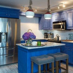Mittelgroße Maritime Küche in L-Form mit profilierten Schrankfronten, blauen Schränken, Marmor-Arbeitsplatte, Küchenrückwand in Weiß, Küchengeräten aus Edelstahl, Kücheninsel und Rückwand aus Metrofliesen in Tampa