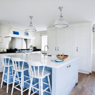 Inspiration for a beach style u-shaped kitchen in Wiltshire with a belfast sink, recessed-panel cabinets, white cabinets, integrated appliances, medium hardwood flooring, an island and brown floors.