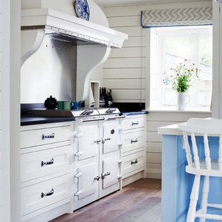 Inspiration for a beach style medium tone wood floor and brown floor kitchen remodel in Wiltshire with a farmhouse sink, recessed-panel cabinets, white cabinets, paneled appliances, quartz countertops and an island