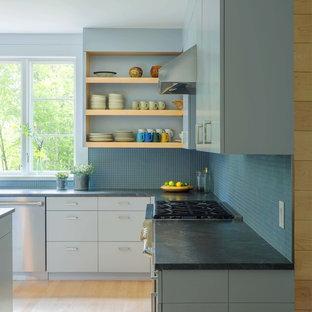 バーリントンの中くらいのモダンスタイルのおしゃれなキッチン (アンダーカウンターシンク、フラットパネル扉のキャビネット、青いキャビネット、御影石カウンター、青いキッチンパネル、ガラスタイルのキッチンパネル、シルバーの調理設備、淡色無垢フローリング) の写真