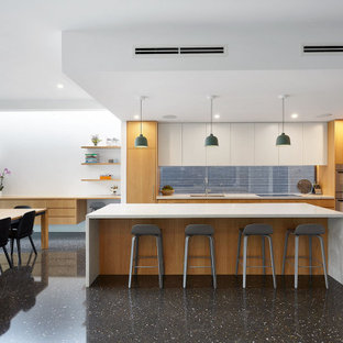 This is an example of a contemporary l-shaped open plan kitchen in Melbourne with a double-bowl sink, flat-panel cabinets, medium wood cabinets, window splashback, stainless steel appliances, with island, black floor and white benchtop.
