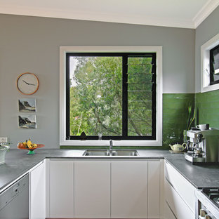 Inspiration for a mid-sized contemporary u-shaped open plan kitchen in Newcastle - Maitland with an undermount sink, white cabinets, quartz benchtops, green splashback, ceramic splashback, stainless steel appliances, medium hardwood floors, a peninsula, brown floor and grey benchtop.