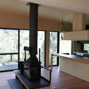 Cette image montre une cuisine linéaire design de taille moyenne avec un évier 3 bacs, des portes de placard noires, un plan de travail en inox, une crédence en fenêtre, un électroménager en acier inoxydable, un sol en bois clair et un îlot central.
