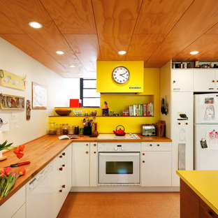 Eclectic kitchen designs - Example of an eclectic l-shaped kitchen design in Seattle with a drop-in sink, flat-panel cabinets, white cabinets, yellow backsplash, white appliances, an island and yellow countertops