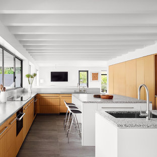 Contemporary open concept kitchen ideas - Example of a trendy l-shaped gray floor open concept kitchen design in Austin with an undermount sink, flat-panel cabinets, medium tone wood cabinets, window backsplash, paneled appliances, two islands and gray countertops