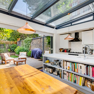 Inspiration for a medium sized modern single-wall kitchen/diner in London with a double-bowl sink, recessed-panel cabinets, white cabinets, quartz worktops, white splashback, metro tiled splashback, stainless steel appliances, light hardwood flooring, an island, beige floors and white worktops.