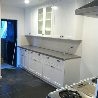 Inspiration for a small contemporary galley separate kitchen in Los Angeles with a double-bowl sink, shaker cabinets, white cabinets, quartzite benchtops, white splashback, ceramic splashback, stainless steel appliances, porcelain floors and no island.