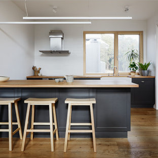 Scandinavian kitchen in Other with a farmhouse sink, shaker cabinets, black cabinets, wood benchtops, white splashback, medium hardwood floors and a peninsula.