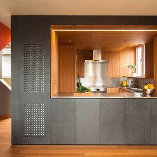 Свежая идея для дизайна: маленькая п-образная кухня в современном стиле с обеденным столом, накладной раковиной, столешницей из нержавеющей стали, фартуком цвета металлик, техникой из нержавеющей стали и полом из бамбука - отличное фото интерьера