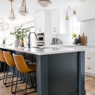 Exempel på ett stort klassiskt vit vitt kök, med en trippel diskho, skåp i shakerstil, vita skåp, bänkskiva i kvarts, vitt stänkskydd, stänkskydd i tunnelbanekakel, rostfria vitvaror, mellanmörkt trägolv, en köksö och brunt golv