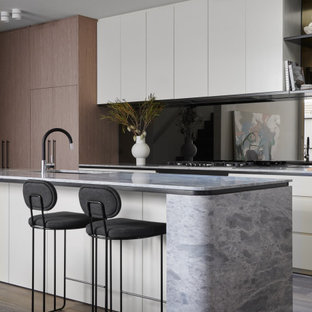 Mid-sized contemporary galley kitchen in Melbourne with a single-bowl sink, flat-panel cabinets, medium wood cabinets, black splashback, glass sheet splashback, panelled appliances, medium hardwood floors, with island, brown floor and grey benchtop.
