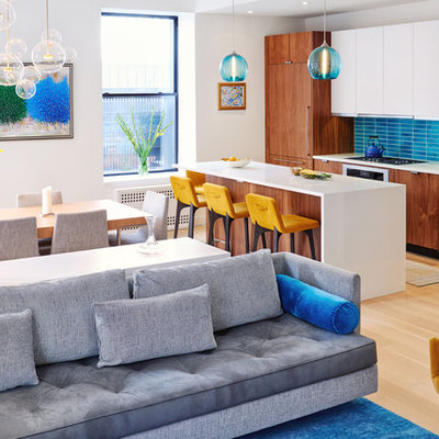 Open concept kitchen - contemporary galley light wood floor and beige floor open concept kitchen idea in New York with flat-panel cabinets, medium tone wood cabinets, blue backsplash, paneled appliances and an island
