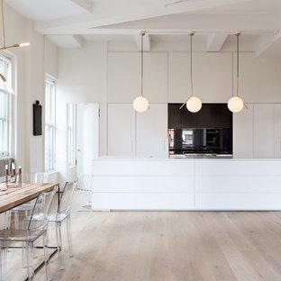 ニューヨークの中くらいの北欧スタイルのおしゃれなキッチン (フラットパネル扉のキャビネット、白いキャビネット、淡色無垢フローリング、人工大理石カウンター、黒いキッチンパネル、シルバーの調理設備、ガラス板のキッチンパネル) の写真