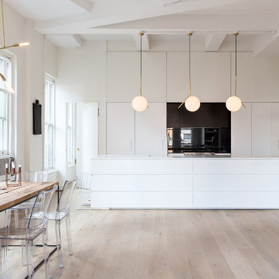 Eat-in kitchen - mid-sized scandinavian galley light wood floor eat-in kitchen idea in New York with flat-panel cabinets, white cabinets, an island, solid surface countertops, black backsplash, stainless steel appliances and glass sheet backsplash