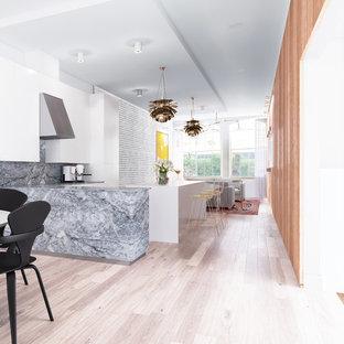 他の地域の大きいエクレクティックスタイルのおしゃれなキッチン (アンダーカウンターシンク、フラットパネル扉のキャビネット、白いキャビネット、大理石カウンター、グレーのキッチンパネル、石タイルのキッチンパネル、シルバーの調理設備の、淡色無垢フローリング、ベージュの床、グレーのキッチンカウンター) の写真
