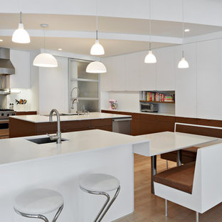 Immagine di una grande cucina moderna con lavello sottopiano, ante lisce, ante bianche, paraspruzzi a effetto metallico, elettrodomestici in acciaio inossidabile, parquet chiaro, top in superficie solida, paraspruzzi con piastrelle di metallo, isola e top bianco