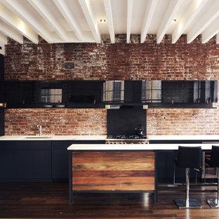 Inredning av ett modernt litet linjärt kök med öppen planlösning, med luckor med glaspanel, svarta skåp, marmorbänkskiva, en köksö, en undermonterad diskho, rött stänkskydd, stänkskydd i tegel, svarta vitvaror, mörkt trägolv och brunt golv
