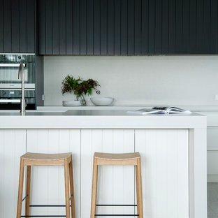 Свежая идея для дизайна: большая угловая кухня-гостиная в морском стиле с врезной раковиной, фасадами в стиле шейкер, черными фасадами, столешницей из кварцевого композита, бежевым фартуком, фартуком из плитки мозаики, черной техникой, полом из терраццо, островом, серым полом и белой столешницей - отличное фото интерьера