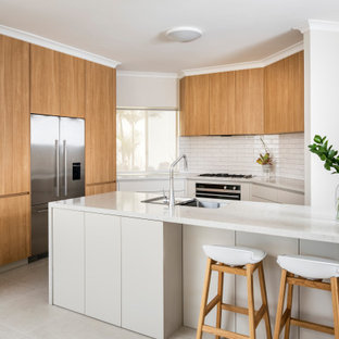 Mid-sized contemporary l-shaped eat-in kitchen in Perth with a double-bowl sink, flat-panel cabinets, grey cabinets, quartz benchtops, white splashback, subway tile splashback, stainless steel appliances, ceramic floors, with island, beige floor and white benchtop.