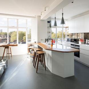Offene Moderne Küche mit Unterbauwaschbecken, flächenbündigen Schrankfronten, weißen Schränken, Rückwand aus Spiegelfliesen, Linoleum, Halbinsel, grauem Boden und weißen Elektrogeräten in London