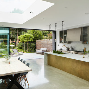 Inspiration for a contemporary open plan kitchen in London with marble worktops, concrete flooring, an island and white splashback.