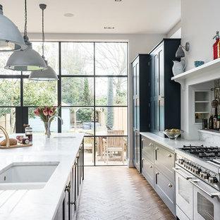 ロンドンの大きいトラディショナルスタイルのおしゃれなキッチン (シェーカースタイル扉のキャビネット、青いキャビネット、大理石カウンター、パネルと同色の調理設備、無垢フローリング、アンダーカウンターシンク) の写真
