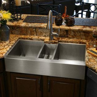 Modelo de cocina comedor moderna, grande, con fregadero de tres senos, puertas de armario de madera en tonos medios, encimera de granito y electrodomésticos de acero inoxidable