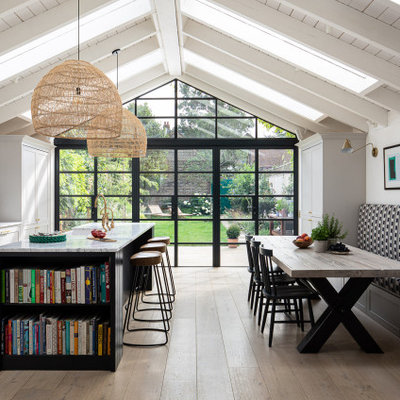 Inspiration for a large transitional light wood floor and beige floor eat-in kitchen remodel in London with a farmhouse sink, shaker cabinets, gray cabinets, black appliances, an island and white countertops
