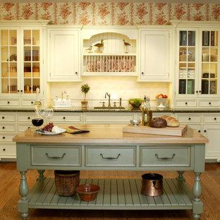 Inredning av ett kök, med luckor med infälld panel, vita skåp, träbänkskiva, vitt stänkskydd och stänkskydd i tunnelbanekakel