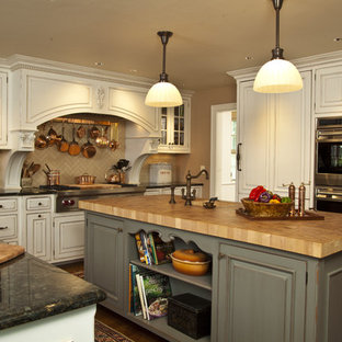 Kitchen - rustic kitchen idea in New York with paneled appliances, subway tile backsplash and wood countertops