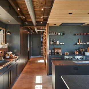 Пример оригинального дизайна: п-образная кухня в стиле лофт с врезной раковиной, плоскими фасадами, серыми фасадами, серым фартуком, техникой из нержавеющей стали, бетонным полом, двумя и более островами, коричневым полом, серой столешницей и деревянным потолком