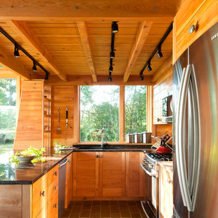 Small rustic kitchen designs - Small mountain style gray floor and slate floor kitchen photo in Portland Maine with granite countertops, stainless steel appliances, an undermount sink, medium tone wood cabinets, window backsplash and a peninsula