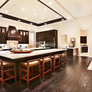 Foto di una grande cucina tropicale con lavello sottopiano, ante con bugna sagomata, ante in legno bruno, top in marmo, paraspruzzi bianco, paraspruzzi in lastra di pietra, elettrodomestici da incasso, parquet scuro e 2 o più isole