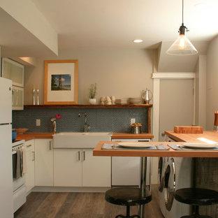 Kleine Moderne Wohnküche in L-Form mit Landhausspüle, Glasfronten, weißen Schränken, Arbeitsplatte aus Holz, Küchenrückwand in Blau, Rückwand aus Keramikfliesen, weißen Elektrogeräten und Halbinsel in Vancouver