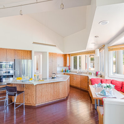 Inspiration for a large contemporary u-shaped dark wood floor eat-in kitchen remodel in Hawaii with flat-panel cabinets, stainless steel appliances, an island, an undermount sink, light wood cabinets and solid surface countertops