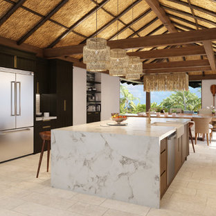 Design ideas for a large tropical open plan kitchen in Hawaii with a farmhouse sink, flat-panel cabinets, dark wood cabinets, quartz benchtops, grey splashback, glass tile splashback, stainless steel appliances, ceramic floors, with island and beige floor.