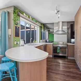 サンシャインコーストのトロピカルスタイルのおしゃれなコの字型キッチン (ダブルシンク、中間色木目調キャビネット、ラミネートカウンター、緑のキッチンパネル、シルバーの調理設備の、クッションフロア、茶色い床、白いキッチンカウンター) の写真