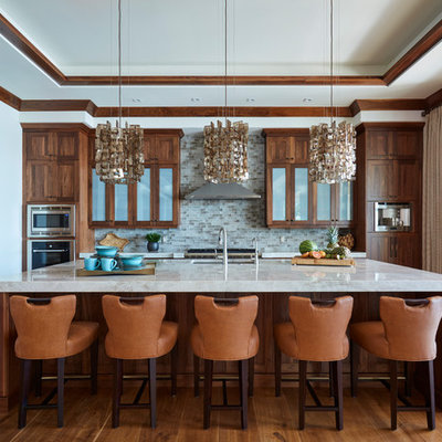 Kitchen - mid-sized tropical l-shaped medium tone wood floor and brown floor kitchen idea in Miami with an undermount sink, medium tone wood cabinets, quartz countertops, mosaic tile backsplash, stainless steel appliances, an island, shaker cabinets and gray backsplash